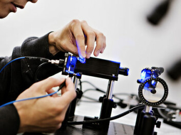 Albert Tsao examines a laser used by researchers to send light pulses along an optical fibre into their study subjects' brains. (Photo: Geir Mogen, NTNU)