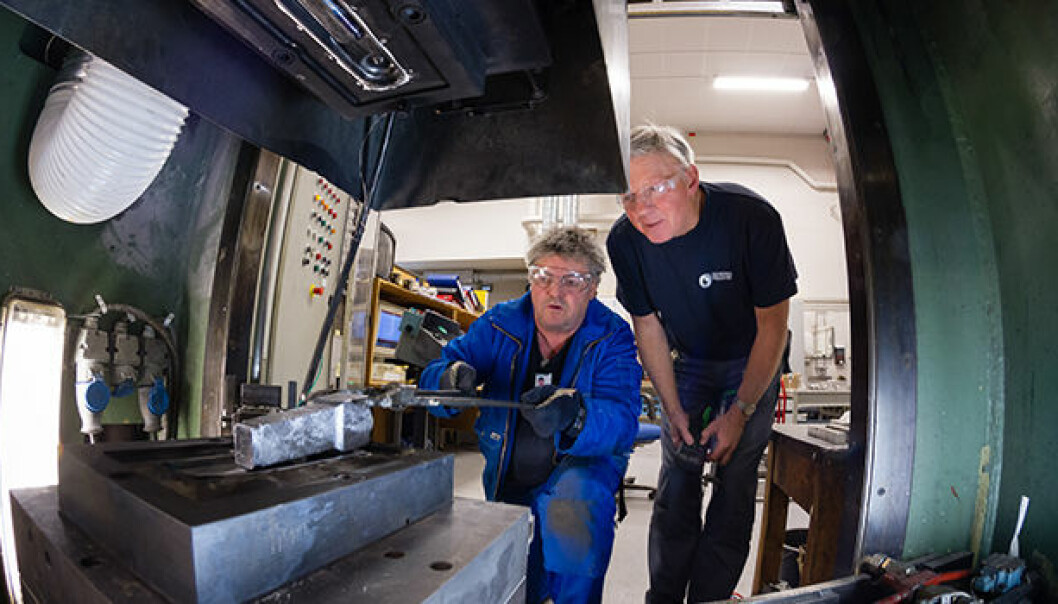 They hope to contribute to energy-efficient manufacture of aluminium vehicle components. Workshop manager Arne Gellein of SINTEF fits the casting into place in the forging machine, together with senior scientist Martin Lefstad. (Photo: SINTEF/Thor Nielsen)