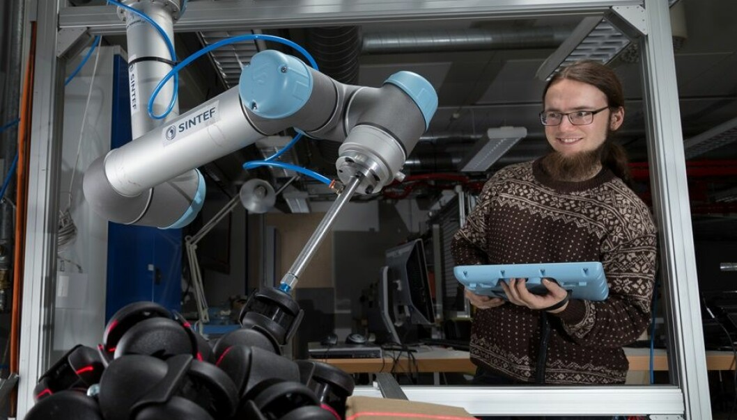 Researcher Sigurd Albrektsen is sitting at a PC that calibrates the settings of two robotic arms and a box of castors. (Photo: SINTEF /Thor Nielsen)