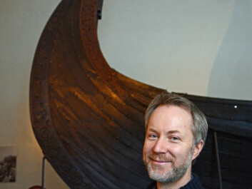 Runologist Jonas Nordby is a code-breaker. The Oseberg Ship behind him also contained one of many riddles from the Viking Era. (Photo: Ida Kvittingen)