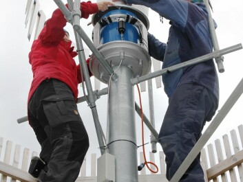 Scientists conduct maintenance work inside one of two wind fences surrounding a precipitation gauge at Haukeliseter. (Photo: Ole Jørgen Østby, Norwegian Meteorological Institute)