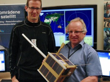 Øystein Helleren (left) and Richard B. Olsen show off a full-scale model of the AISSat-1 in the control room of the Norwegian Defence Research Establishment, where signals from the satellite are monitored. The satellite is a cube, 20x20x20 cm, and the silver pole sticking out is the antenna that catches signals from ships. (Photo: Arnfinn Christensen, forskning.no)