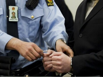 16 April 2012. Police unlock handcuffs on Anders Behring Breivik on the first day of his trial in the Oslo Courthouse. (Photo: Heiko Junge / NTB Scanpix)