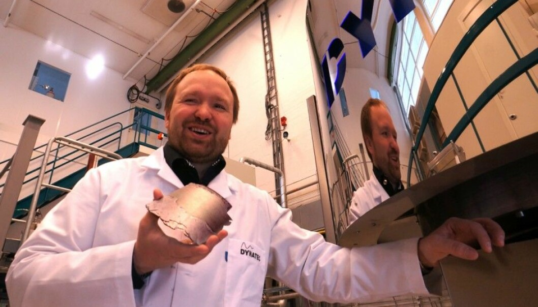 The new version of the Danatec company's centrifuge can produce pure silicon without cooling the hardware. It thus produces silicon 40 times faster than in traditional production machinery. Research manager Werner Filtvedt at Dynatec shows off a piece of silicon retrieved from the curved inner wall of the centrifuge behind him. (Photo: Arnfinn Christensen)