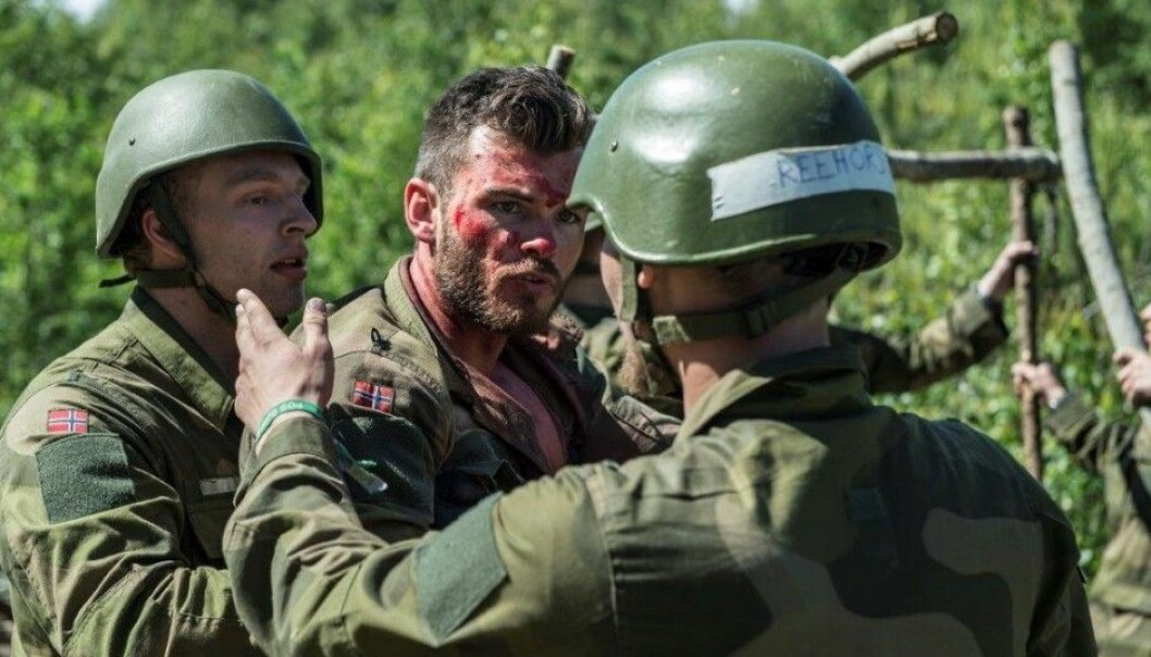 """Two candidates try to treat a """"injured"""" soldier during the application process to the Norwegian Armed Forces officer training programme. (Photo: Norwegian Armed Forces)"""