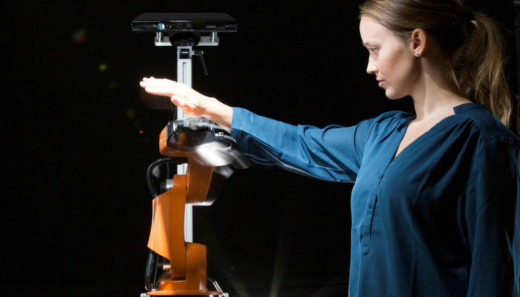 Researcher Marianne Bakken attempting to get close and personal with an orange robot arm – moving in all directions to try to get the robot to collide with her. But it manages to avoid her every time. (Photo: Werner Juvik)