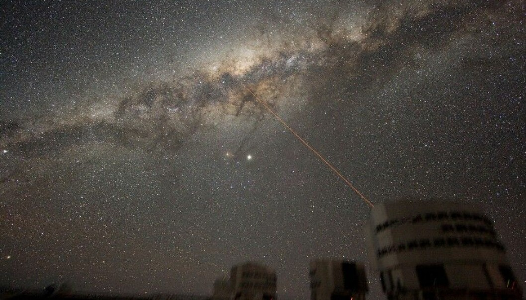 This is the Milky Way in all its glory, as seen from Earth. Could someone be out there trying to contact us? The image shows the ESO VLT telescope. The laser beam in the illustration is from the telescope. (Illustration: Y.Beletsky / ESO / CC BY 3.0)