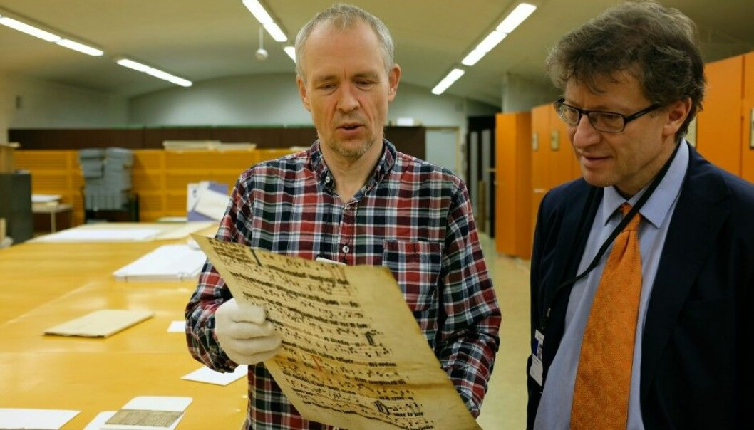 Tor Weidling (left) and Espen Karlsen work together searching for fragments of old documents. This one is from the 1300s. (Photo: Silja Björklund Einarsdóttir/forskning.no)