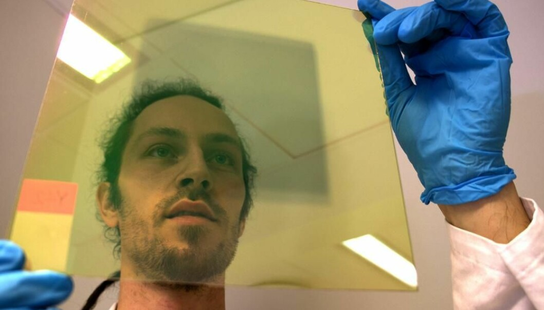 Researcher Trygve Mongstad studying a glass plate coated with a thin layer of vaporised metal hydride, a chemical compound consisting of yttrium and hydrogen, which darkens when struck by light. (Photo: Arnfinn Christensen)