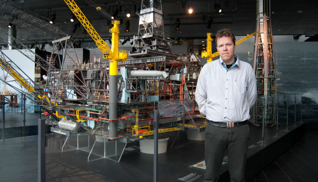 The two-meter tall researcher Gunleiv Hadland at the Norwegian Petroleum Museum in Stavanger poses in front of the Statfjord B model. (Photo: Marianne Nordahl)