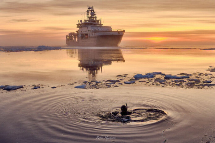 Avatar Alliance Foundation photographer Lu Lamar tests a dive suit in front of icebreaker Kronprins Haakon. The location is 4000 metres above the Aurora volcanic field.