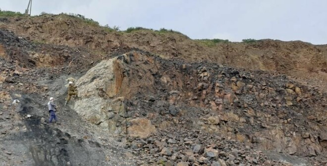 Geologists conducting field surveys in the Central Siberian Plateau. The photo shows a magmatic rock (intrusion) that has penetrated into sedimentary rocks that in the area have several layers of coal.