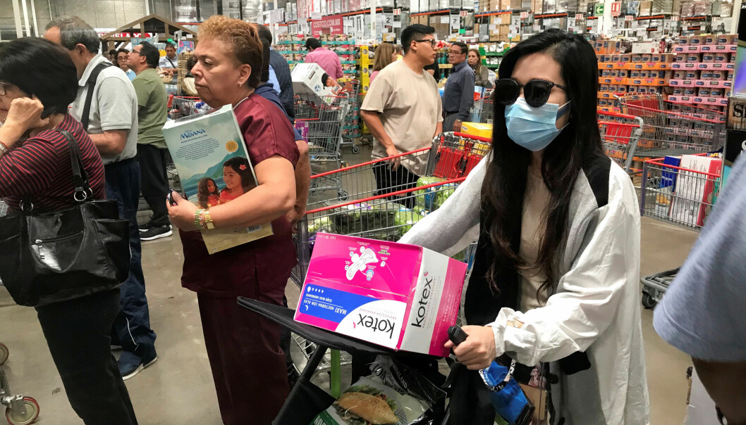 A woman wears a protective mask as she and others wait to pay at a supermarket during an outbreak of the coronavirus (COVID-19) in Mexico City, Mexico March 13, 2020.