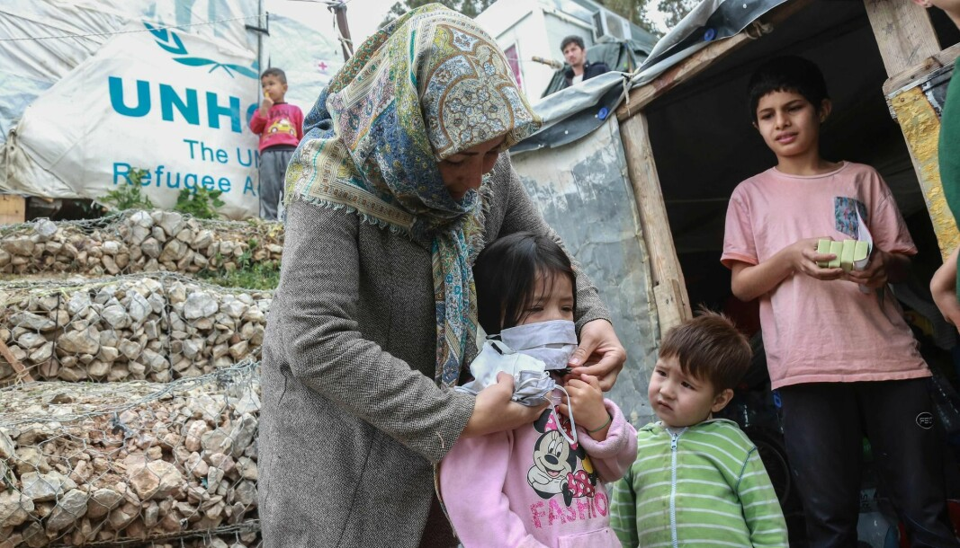 """A woman helps a child with a mask after members of NGO """"Team Humanity"""" gave out handmade protective face masks to migrants and refugees in the camp of Moria in the island of Lesbos on March 28, 2020 as as the country is under lockdown to stop the spread of Covid-19 disease caused by the novel coronavirus."""