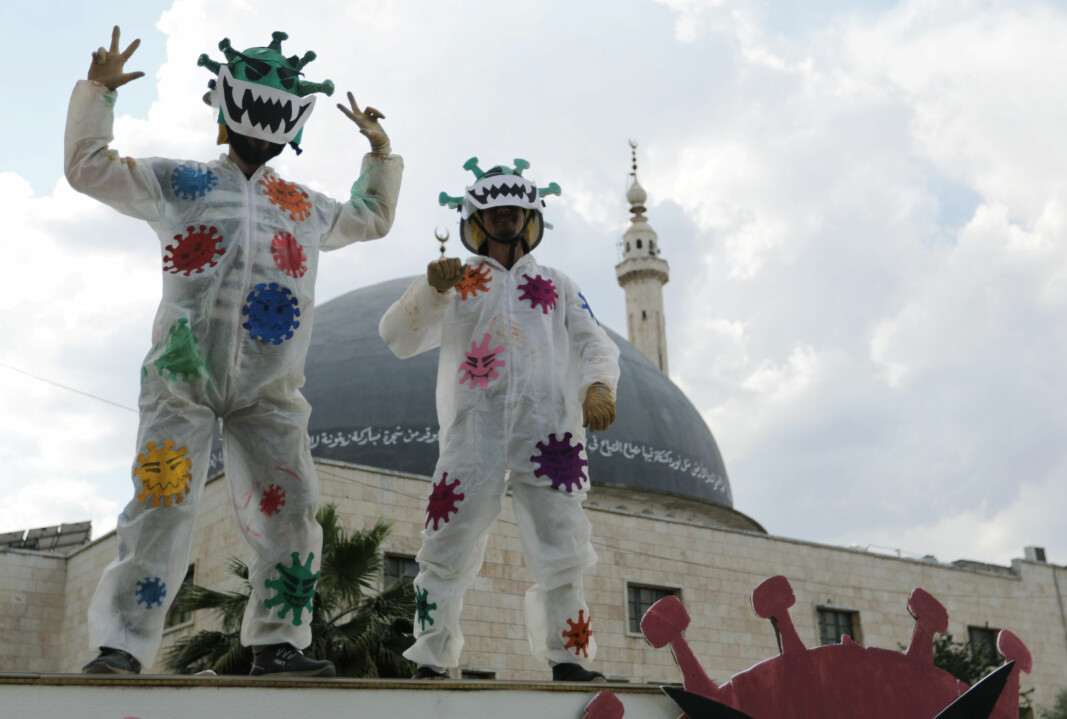 Volunteers dressed in coronavirus-themed costumes gesture as they stand on a vehicle during a campaign organised by the Violet Organization, in an effort to spread awareness and encourage safety amid coronavirus disease (COVID-19) fears, in the rebel-held Idlib city, Syria April 29, 2020.