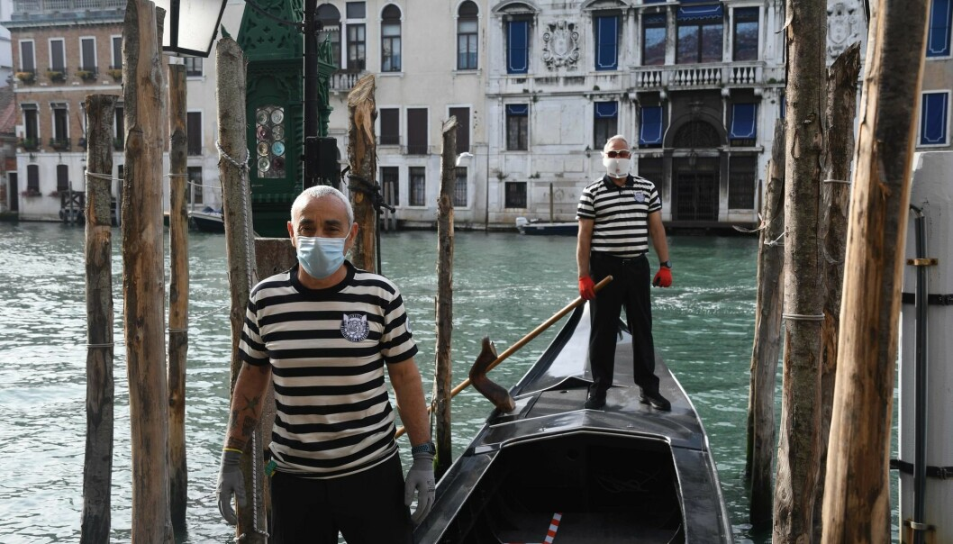 The use of face masks was made mandatory on public transport and in stores in Italy as the country gradually loosend lockdown measures. Gondoliers wearing a face mask stand on a gondola on a Venice canal as they resumed their service on May 18, 2020.