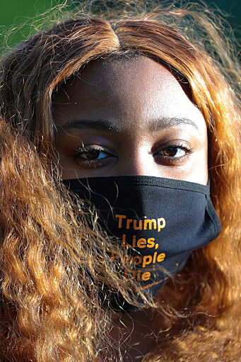 "A demonstrator wears a custom face mask reading ""Trump Lies, People Die"" during a funeral procession demonstration for COVID-19 victims outside of the White House in Washington, U.S., May 20, 2020. Americans of colour, particularly black men, have shared their fears of wearing face masks in public and being mistaken for criminals."