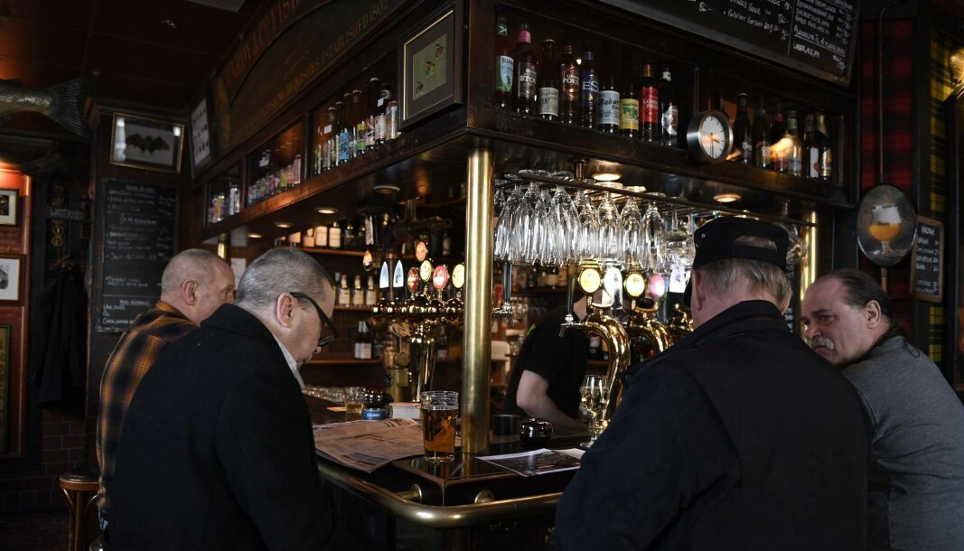 Men drinking beer in a bar in Stockholm 23 March this year. While Oslo's beer taps closed, restaurants and bars have stayed open in Sweden despite the coronavirus crisis.