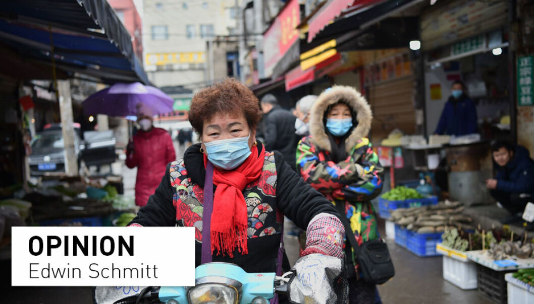 A woman wearing a facemask to help stop the spread of a deadly virus which began in the city rides her scooter through a market in Wuhan on January 24, 2020. Chinese people have since the start of the pandemic reported incidents of racism connected to the coronavirus and its origins all over the world, including in Norway.