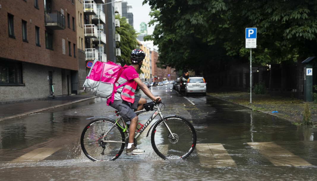 A Norwegian food delivery driver for Foodora working after heavy rainfall.