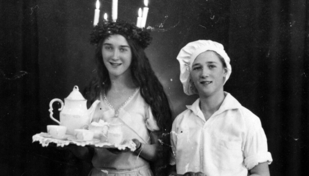 A Lucia girl and a baker boy serve coffee and saffron buns in a Swedish home in 1933.