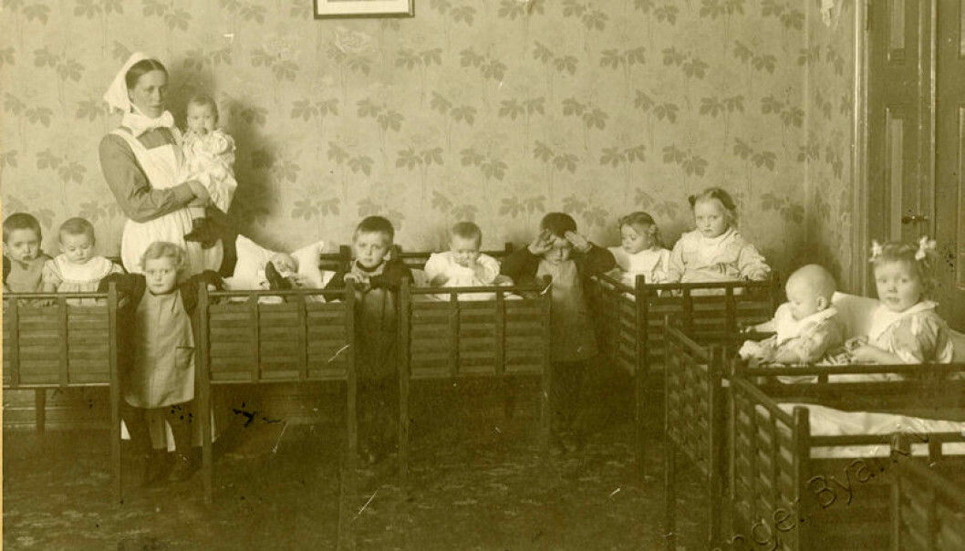 The Cathedral crèche in Stavanger 1919: The picture shows a ward sister and the children in the dormitory. This institution continued to be run by a female deacon or ward sister until 1970.