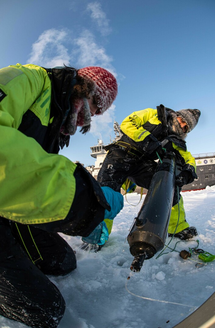 Cheshtaa (to the right) working on the sea ice, retrieving a water sampling bottle from an ice hole