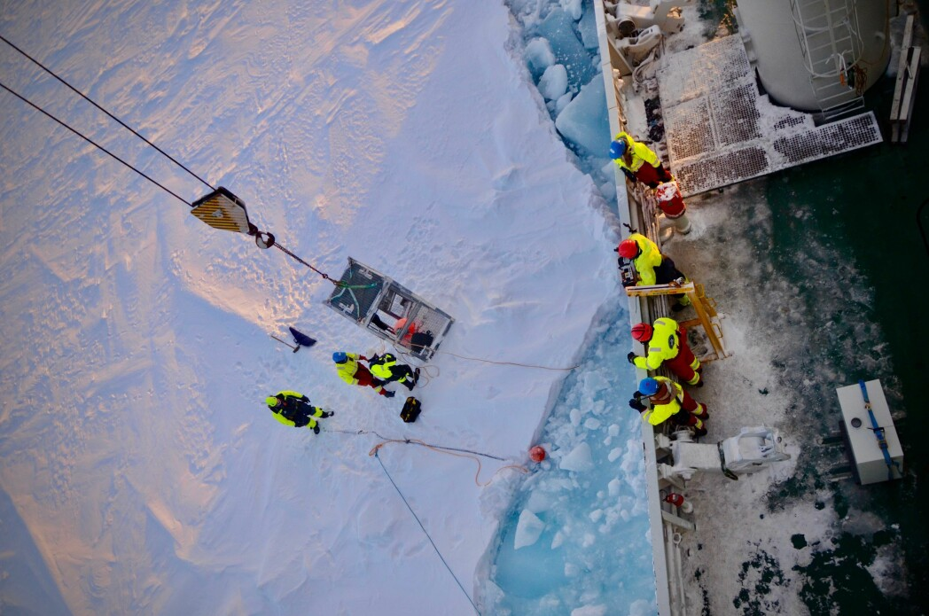 Attaching the sediment traps to an ice floe: Martí, Yasemin and Jørn as a polar bear guard are lifted onto the ice to secure the traps.