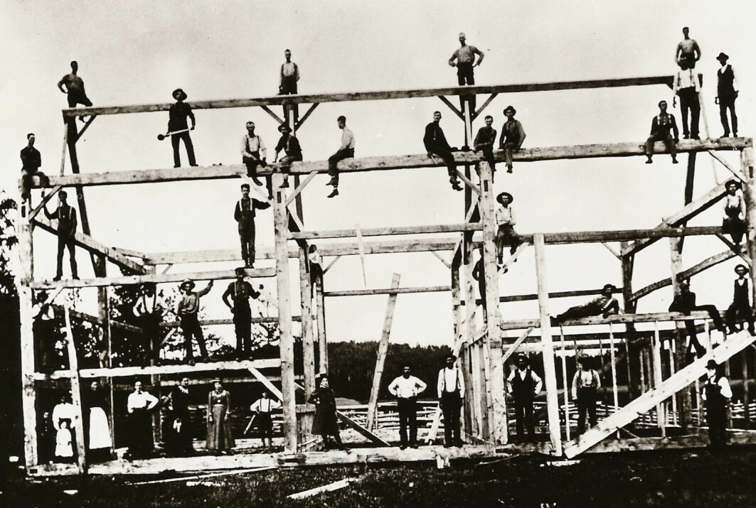 """When families found a suitable place to establish themselves, they needed help with construction. This picture is from Montana in 1895 and shows a barn under construction, apparently in good Norwegian <span class="""" italic"""" data-lab-italic_desktop=""""italic"""">dugnad </span>– or volunteering – tradition."""