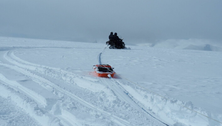 A snowmobile towing georadar equipment.