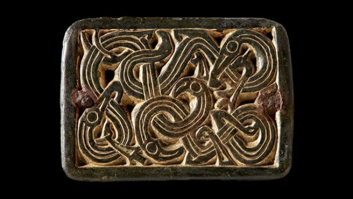 Buckle with snake-like animals from the Merovingian period (ca. 550-800 AD). The buckle is made of copper alloy and is gilded with gold. It was originally attached to a harness or a belt with small rivets in the corners, but later had a fastening mounted on the back and was used as a buckle, probably on a woman's costume.