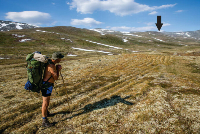 Reidar Marstein by the tracks leading to the Lendbreen pass. Check the many track marks. The pass is marked with an arrow.