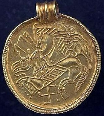 A typical Scandinavian gold braided bracteate with a figure of a horse and reverse swastika at the bottom. The runes on the bracteate say Alu. The bracteate is from the time around to the climate disaster. The swastika is an ancient symbol in many cultures, including in Scandinavia. This bracteate was found in Sweden.